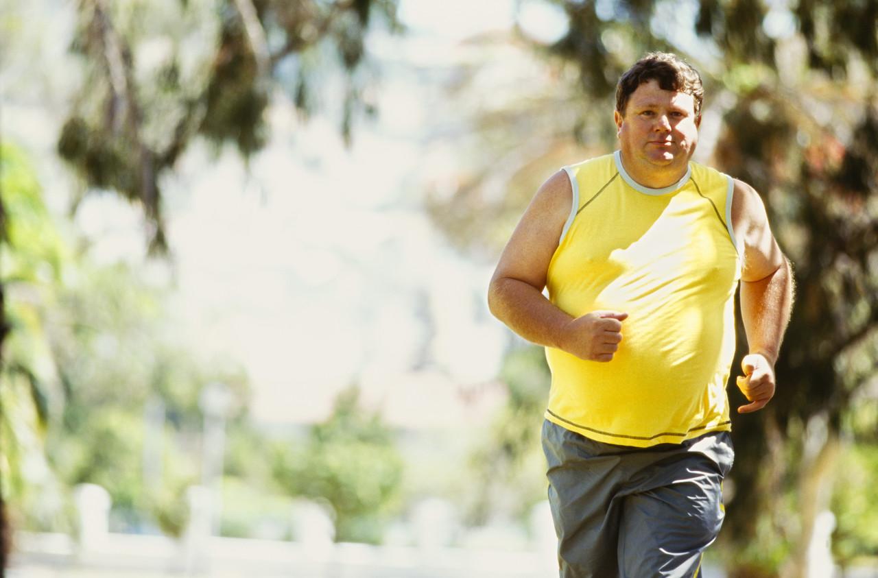 портрет бегущего полного мужчины в парке