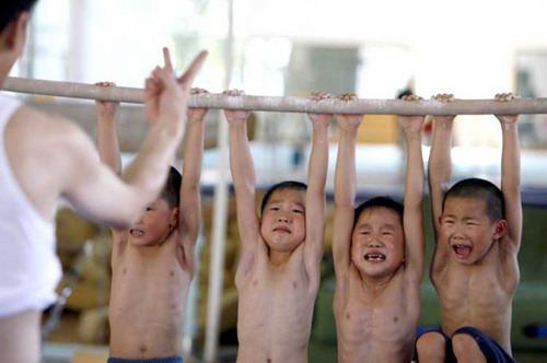 A coach counts down the time as boys hang on a bar for five minutes as part of a training session at the Gymnastics Hall of the Shanghai University of Sports