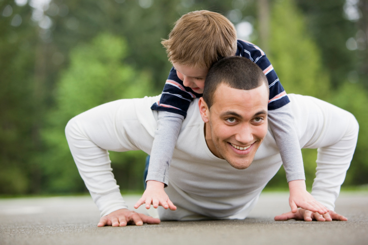 Boy Laying on Man Doing Pushups