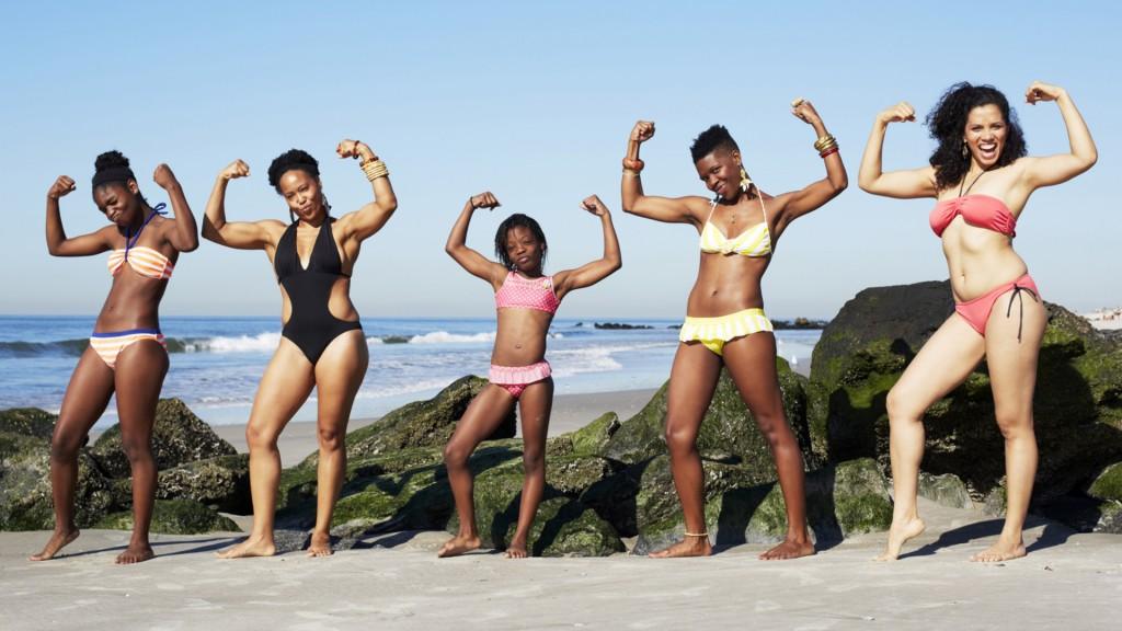 women-striking-power-pose-on-beach