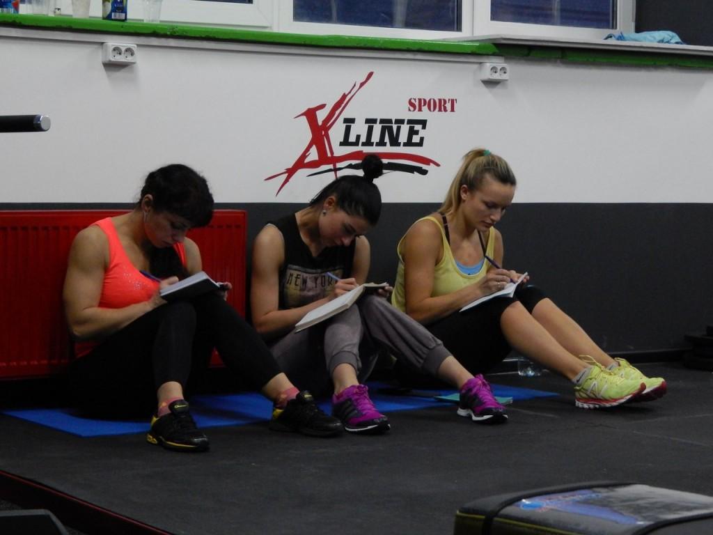 девушки записывают свои упражнения в дневник тренировок