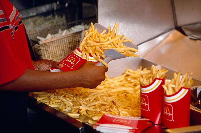 """Сотрудник чикагского """"Макдоналдса"""" готовит заказ на картофель фри, 12 июля 1990 года Фото: Ralf-Finn Hestoft / Corbis / Vida Press"""