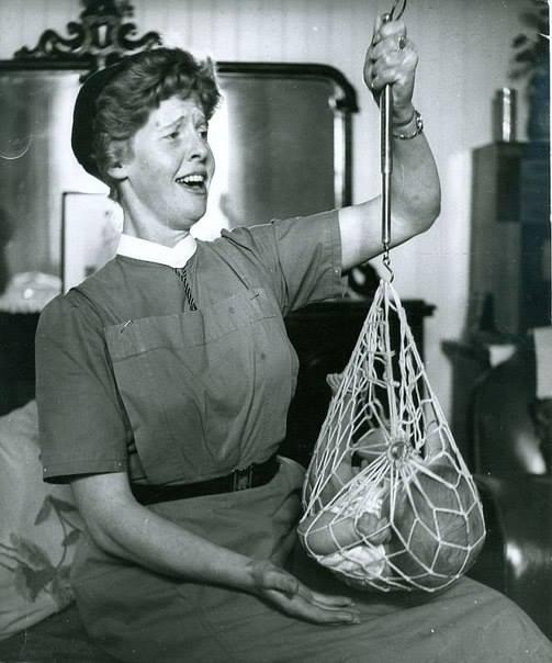 Медсестра Катриона Макаскилл взвешивает новорожденного ребенка, 1959 год, Шотландия