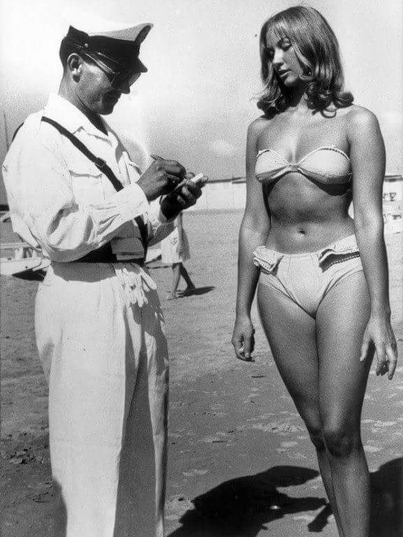 Полицейский улыбается и выписывает штраф женщине за ношение бикини на пляже, 1957 год, Римини, Италия